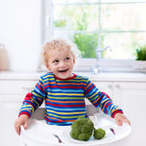 Little boy eating broccoli in white kitchen Stock Images