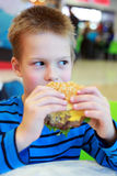 Little boy eating burger Stock Image