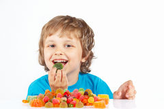 Little boy eating candies on white background Stock Images