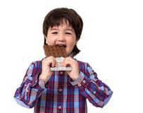 Little boy eating chocolate Stock Image
