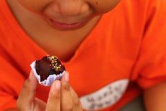 Little boy eating chocolate, outdoor. Little boy eating chocolate ball yummy,outdoor Royalty Free Stock Image