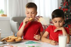 Little boy eating cookies while his friend drawing picture. Ttle boy eating cookies while his friend drawing picture at home. Children celebrating Christmas stock photos