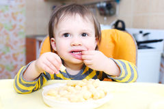 Little boy eating corn curls Stock Images