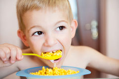 Little boy eating corn flakes with milk Stock Image