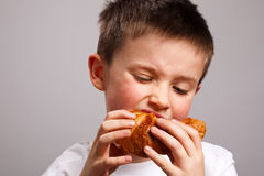 Little boy eating a croissant Stock Photos