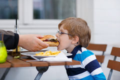 Little boy eating fast food: french fries and hamburger Royalty Free Stock Photography