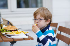 Little boy eating fast food: french fries and hamburger Stock Photos