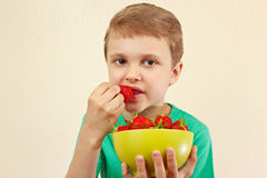 Little boy eating fresh sweet strawberries from bowl. Little boy eating fresh sweet strawberries from a bowl Royalty Free Stock Image