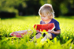 Little boy eating fresh watermelon outdoors Stock Photo