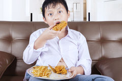 Little boy eating fried chicken at home Stock Photography