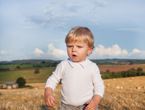 Little boy eating German sausage on goden hay field Stock Photos