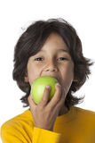 Little boy eating a green aplle Stock Photo