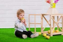 Little boy eating a green apple Stock Photo