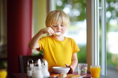 Little boy eating healthy breakfast in hotel restaurant. Tasty meal in home. Healthy food for kids royalty free stock image