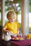 Little boy eating healthy breakfast in hotel restaurant. Tasty meal in home. Healthy food for kids stock images