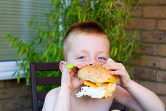 Little boy eating a huge burger Stock Photo