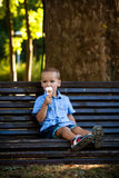 Little boy eating ice cream in park summer day Royalty Free Stock Image