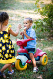 Little boy eating ice cream sit on small tricycle while his sist Royalty Free Stock Photo