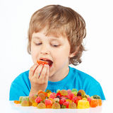 Little boy eating jelly candies on white background Stock Photo
