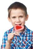 Little boy eating lollipop heart Stock Photography
