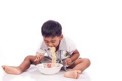 Little boy eating noodle Stock Images