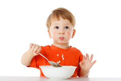 Little boy eating the oatmeal Royalty Free Stock Image