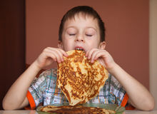 Little boy is eating pancakes Stock Photography