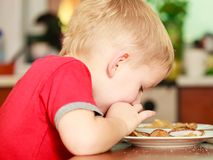 Little boy eating pancakes for breaktfast royalty free stock photo