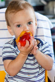 Little boy eating a peach Stock Image