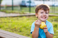 Little boy eating pear Royalty Free Stock Image