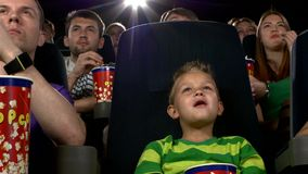 Little boy eating popcorn and watching movie at