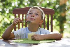Little boy eating pudding Stock Image