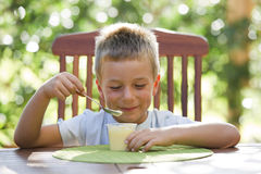 Little boy eating pudding Stock Images