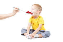 Little boy is eating raspberries, isolated over white Stock Photos
