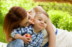 Little boy eating red apple Stock Images