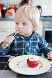 Little boy eating red cupcake Stock Image