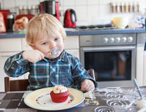 Little boy eating red cupcake Royalty Free Stock Images
