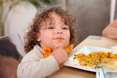 Little boy eating rice= royalty free stock photography