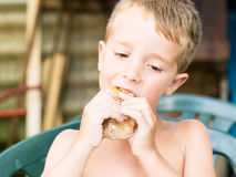 Little boy eating a sandwich Stock Photo
