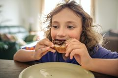 Cute little boy eating lunch at his dining room table royalty free stock photography