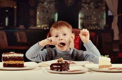 Little boy eating a slice of cake with gusto Stock Image