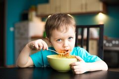 Little boy is eating spaghetti Stock Photos