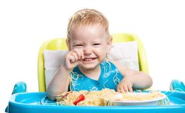 Little boy eating spaghetti and laughing Stock Image