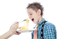 Little boy is eating spaghetti using fork Stock Photos