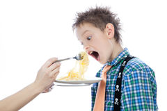 Little boy is eating spaghetti using fork Royalty Free Stock Photos