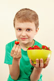 Little boy eating sweet red strawberries from bowl Royalty Free Stock Image