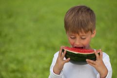 Little boy eating a watermelon stock photos