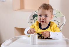 Little boy is eating yogurt for Breakfast. Himself Royalty Free Stock Photo