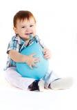 Little boy eats blue baloon. Little boy eats and hugs blue baloon and smiling Royalty Free Stock Photos