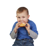 Little boy eats bun Stock Photos